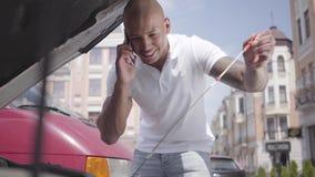 Πίσω άποψη του φαλακρού Μεσο-Ανατολικού ατόμου που κοιτάζει κάτω από την κουκούλα αυτοκινήτων που μιλά με το τηλέφωνο κυττάρων Ο  φιλμ μικρού μήκους