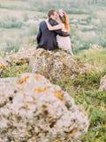 Πίσω άποψη του φιλήματος newlyweds καθμένος στο βράχο στοκ εικόνες