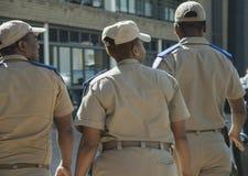 Πίσω άποψη τριών νοτιοαφρικανικών ανώτερων υπαλλήλων κυκλοφορίας, ένα θηλυκό και δύο αρσενικά, που φορούν τα καλύμματα Στοκ εικόνα με δικαίωμα ελεύθερης χρήσης