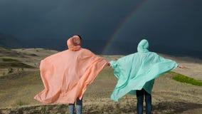Πίσω άποψη των ανθρώπων που φορούν τα ζωηρόχρωμα αδιάβροχα που θέτουν με τα χέρια χώρια στο υπόβαθρο του ουρανού με το ουράνιο τό απόθεμα βίντεο