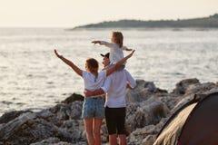 Πίσω άποψη των ευτυχών γονέων με λίγη κόρη, που κάθεται στο λαιμό μπαμπάδων Στοκ Εικόνες