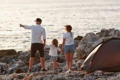 Πίσω άποψη των ευτυχών νέων γονέων, που κρατούν την κόρη χεριών, που στέκεται στην παραλία βράχου Στοκ φωτογραφία με δικαίωμα ελεύθερης χρήσης