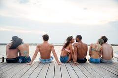 Πίσω άποψη των ζευγών που κάθονται και που αγκαλιάζουν στην αποβάθρα Στοκ Φωτογραφία
