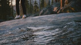Πίσω άποψη των θηλυκών ποδιών που πηδά πέρα από ένα μικρό ρεύμα νερού, κορίτσι που περπατά επάνω στην άκρη βράχου στο πάρκο Yosem φιλμ μικρού μήκους