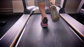 Πίσω άποψη των θηλυκών ποδιών που περπατούν και που τρέχουν treadmill στη γυμναστική, κατάρτιση γυναικών απόθεμα βίντεο