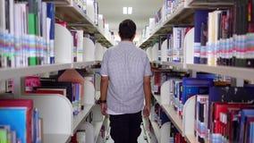 Πίσω άποψη των περιπάτων φοιτητών πανεπιστημίου στη βιβλιοθήκη απόθεμα βίντεο