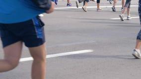 Πίσω άποψη των ποδιών πολλών αθλητικών ανθρώπων που τρέχουν έναν μαραθώνιο στους ανταγωνισμούς απόθεμα βίντεο