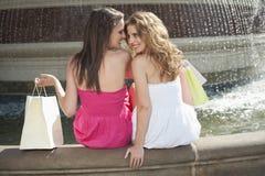 Πίσω άποψη δύο νέων θηλυκών φίλων που επικοινωνούν καθμένος από την πηγή νερού Στοκ φωτογραφία με δικαίωμα ελεύθερης χρήσης