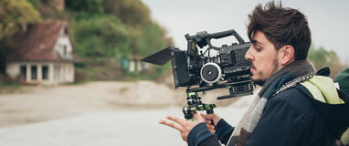 πίσω από τη σκηνή Σκηνή ταινιών πυροβολισμού καμεραμάν με τη κάμερα του Στοκ Εικόνες