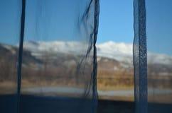 πίσω από τις κουρτίνες Ένας μουντός υπαινιγμός μιας καλής άποψης στοκ εικόνα
