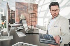 πίσω από το γυαλί σοβαρός επιχειρηματίας με τη συνεδρίαση υπολογιστών στο γραφείο του Στοκ Φωτογραφία