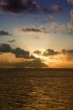 πίσω από το σκοτάδι σύννεφων πέρα από το ηλιοβασίλεμα θάλασσας Στοκ Εικόνα