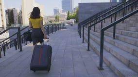 Πίσω ασιατική επιχειρησιακή γυναίκα άποψης με τη βαλίτσα απόθεμα βίντεο