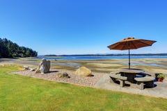Πίσω αυλή με το επιτραπέζιο σύνολο patio πετρών και την άποψη νερού Στοκ Εικόνες