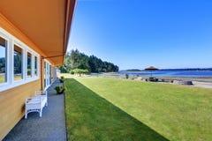 Πίσω αυλή με το επιτραπέζιο σύνολο patio πετρών και την άποψη νερού Στοκ εικόνες με δικαίωμα ελεύθερης χρήσης