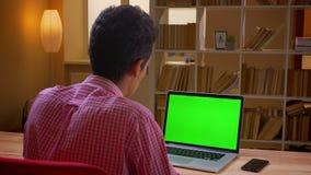 Πίσω βλαστός άποψης κινηματογραφήσεων σε πρώτο πλάνο του ινδικού νέου επιχειρηματία που έχει μια τηλεοπτική κλήση στο lap-top με  απόθεμα βίντεο