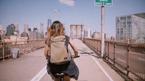 Πίσω γυναίκα ανεξάρτητος εργαζόμενος άποψης με τη μακριά πετώντας τρίχα που απολαμβάνει το γύρο ποδηλάτων Σαββατοκύριακου στη γέφ απόθεμα βίντεο
