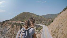 Πίσω γυναίκα τουριστών άποψης νέα με το σακίδιο πλάτης που εξετάζει κάτω στο επικό τοπίο το σημείο γεφυρών φαραγγιών Bixby σε ηλι απόθεμα βίντεο