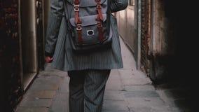 Πίσω επιχειρηματίας άποψης με το σακίδιο πλάτης που φορά το μοντέρνο κοστούμι που περπατά κατά μήκος της σκοτεινής οδού στη Βενετ απόθεμα βίντεο