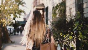 Πίσω ευτυχές καυκάσιο κορίτσι άποψης με την πετώντας τρίχα που περπατά κατά μήκος της ηλιόλουστης οδού πόλεων, περιστασιακός τρόπ απόθεμα βίντεο