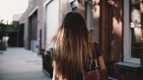 Πίσω ευτυχής ευρωπαϊκή γυναίκα ανεξάρτητος εργαζόμενος άποψης με την τρίχα που φυσά στον αέρα που περπατά κατά μήκος της οδού πόλ απόθεμα βίντεο