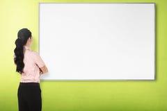 Πίσω νέα γυναίκα άποψης με το λευκό πίνακα Στοκ εικόνα με δικαίωμα ελεύθερης χρήσης
