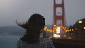 Πίσω νέα όμορφη γυναίκα άποψης που στέκεται μόνο, που εξετάζει γύρω τη σκοτεινή θυελλώδη χρυσή άποψη φωτεινών σηματοδοτών γεφυρών απόθεμα βίντεο