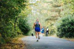 Πίσω παλαιότερος αρσενικός μαραθώνιος δρομέων που τρέχει στο πάρκο φθινοπώρου Στοκ Φωτογραφίες