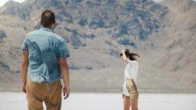 Πίσω περίπατος ζευγών άποψης ρομαντικός που κρατά μαζί τα χέρια προς το επικό άσπρο επίπεδο έδαφος στη μέση της αλατισμένης ερήμο απόθεμα βίντεο