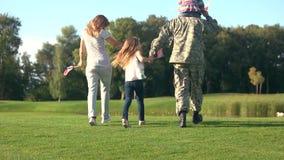 Πίσω περπατώντας οικογένεια άποψης με τον πατέρα στο στρατιωτικό camoubackgrounde απόθεμα βίντεο