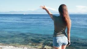 Πίσω πλάγια όψη του κοριτσιού που στέκεται στην ακτή και που κυματίζει για να στείλει σε ωκεάνιο, σε αργή κίνηση απόθεμα βίντεο