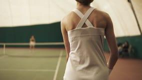 Πίσω πλευρά από το κατώτατο ανοδικό μήκος σε πόδηα ενός ενεργού θηλυκού τενίστα Γήπεδο αντισφαίρισης, στο εσωτερικό, κινηματογράφ φιλμ μικρού μήκους