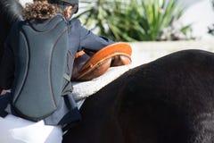 Πίσω πλευρά του νέου κοριτσιού που προετοιμάζει ένα άλογο σελών πριν από ένα Equest στοκ φωτογραφία με δικαίωμα ελεύθερης χρήσης