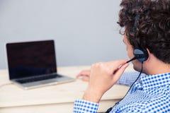 Πίσω πορτρέτο άποψης ενός αρσενικού χειριστή με τα ακουστικά Στοκ Εικόνα