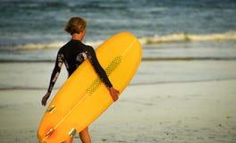 Πίσω πορτρέτο άποψης του νέου ευτυχούς περπατήματος κοριτσιών surfer προς τη θάλασσα που φέρνει τον κίτρινο πίνακα κυματωγών και  στοκ εικόνα με δικαίωμα ελεύθερης χρήσης