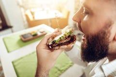 Πίσω σάντουιτς δαγκωμάτων ατόμων άποψης που στον καφέ στοκ εικόνα
