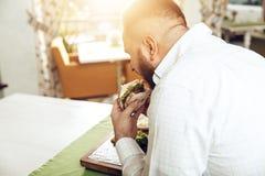 Πίσω σάντουιτς δαγκωμάτων ατόμων άποψης που στον καφέ στοκ φωτογραφίες