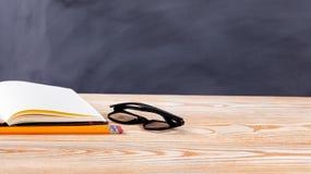 Πίσω στα σχολικά βασικά αντικείμενα μπροστά από το σβημένο μαύρο πίνακα κιμωλίας Στοκ Εικόνα