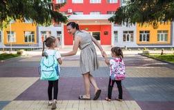 Πίσω στην έννοια σχολικής εκπαίδευσης με τα παιδιά κοριτσιών, στοιχειώδεις σπουδαστές, φέρνοντας σακίδια πλάτης που πηγαίνουν στη στοκ φωτογραφίες