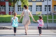 Πίσω στην έννοια σχολικής εκπαίδευσης με τα παιδιά κοριτσιών, στοιχειώδεις σπουδαστές, φέρνοντας σακίδια πλάτης που πηγαίνουν στη στοκ εικόνα