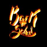 Πίσω στην εγγραφή σχολικών λέξεων που γίνεται από την πυρκαγιά ή τη φλόγα που απομονώνεται στο μαύρο υπόβαθρο Στοκ Εικόνες