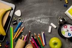 Πίσω στη σχολική έννοια με το σημειωματάριο μήλων μολυβιών κιμωλίας χρώματος ρολογιών πέρα από το υπόβαθρο πινάκων κιμωλίας Στοκ Εικόνες