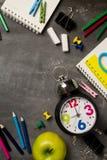 Πίσω στη σχολική έννοια με το σημειωματάριο μήλων μολυβιών κιμωλίας χρώματος ρολογιών πέρα από το υπόβαθρο πινάκων κιμωλίας Στοκ φωτογραφίες με δικαίωμα ελεύθερης χρήσης