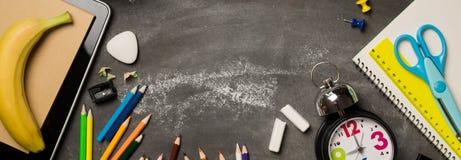 Πίσω στη σχολική έννοια με το σημειωματάριο μήλων μολυβιών κιμωλίας χρώματος ρολογιών πέρα από το υπόβαθρο πινάκων κιμωλίας Στοκ Εικόνα