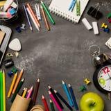 Πίσω στη σχολική έννοια με το σημειωματάριο μήλων μολυβιών κιμωλίας χρώματος ρολογιών πέρα από το υπόβαθρο πινάκων κιμωλίας Στοκ Φωτογραφία
