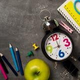 Πίσω στη σχολική έννοια με το σημειωματάριο μήλων μολυβιών κιμωλίας χρώματος ρολογιών πέρα από το υπόβαθρο πινάκων κιμωλίας Στοκ εικόνες με δικαίωμα ελεύθερης χρήσης