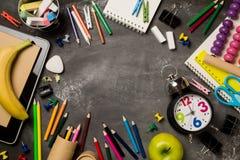 Πίσω στη σχολική έννοια με το σημειωματάριο μήλων μολυβιών κιμωλίας χρώματος ρολογιών πέρα από το υπόβαθρο πινάκων κιμωλίας Στοκ εικόνα με δικαίωμα ελεύθερης χρήσης