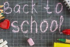 Πίσω στη σχολική έννοια: σχολικές προμήθειες σε έναν πίνακα κιμωλίας στοκ εικόνες