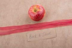 Πίσω στη σχολική εγγραφή με το μήλο και μια κορδέλλα Στοκ φωτογραφίες με δικαίωμα ελεύθερης χρήσης