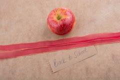 Πίσω στη σχολική εγγραφή με το μήλο και μια κορδέλλα Στοκ Εικόνες